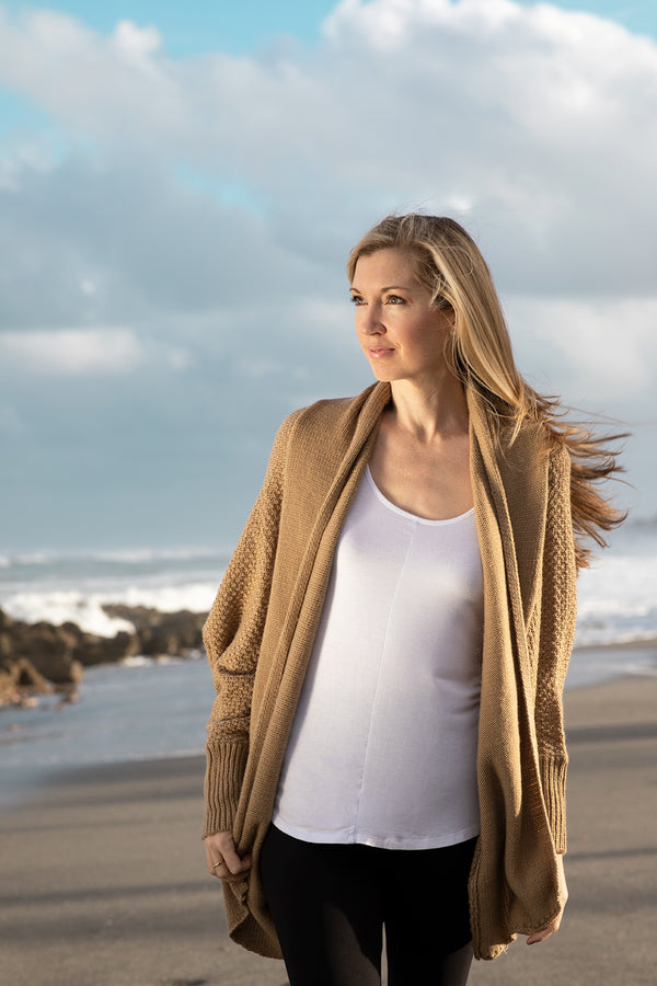 Model at the beach wearing the Zeville Tan cardigan.