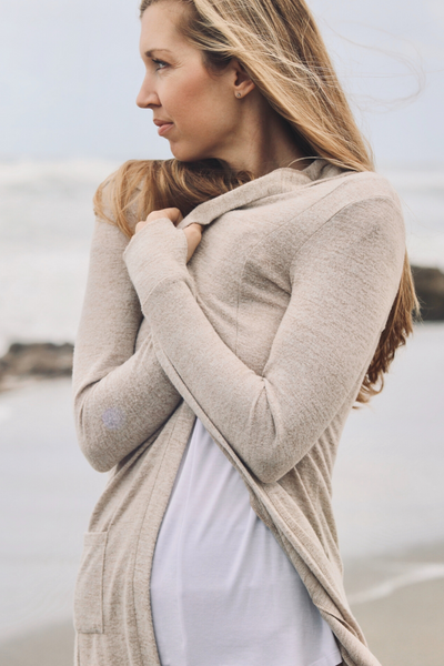 model wearing Feny cardigan. Holding cardigan close to chest. at the beach