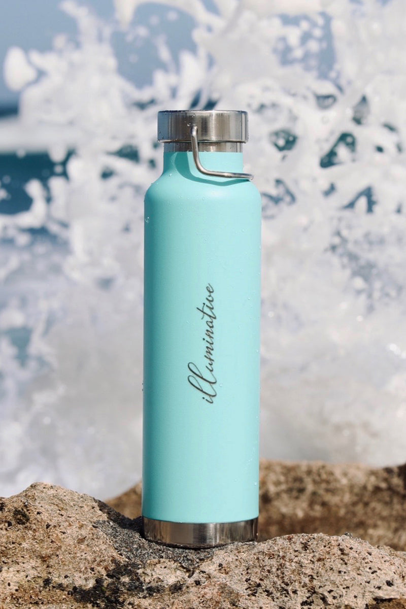 turquoise water bottle with illuminative log sitting on rock at the beach with the waves splashing up.