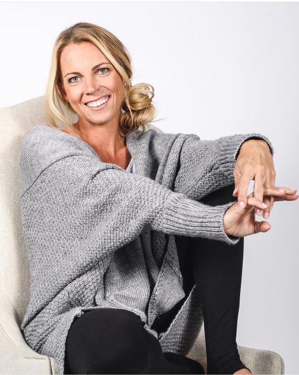 Model sitting in chair wearing grey Zeville cardigan and black leggings.