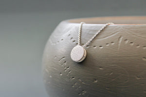 tiny round necklace in sterling silver with textured surface