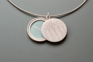 minimalistic silver locket for a picture with forest design