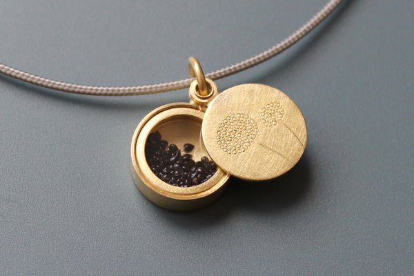 golden dandelion locket filled with forget me not seeds