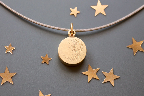 golden floating locket with shooting star