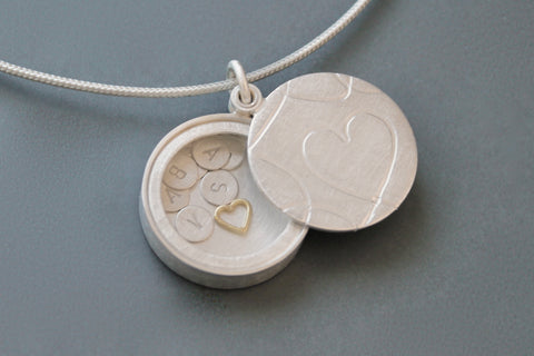 secret silver heart locket filled with letter plates and a golden heart