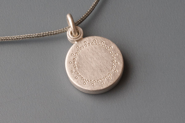 small silver locket with delicate lace patter