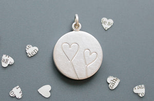 romantic silver photo locket with symbolic two hearts design