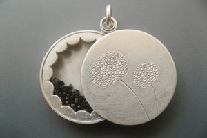 elegant floating locket filled with forget-me-not-seeds in sterling silver with dandelions design