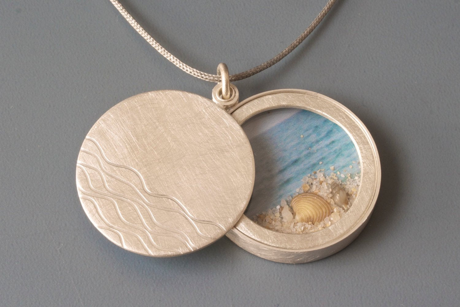maritime floating locket filled sand and seashells handmade in sterling silver