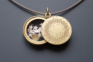 unique golden glass locket filled with sun moon and stars