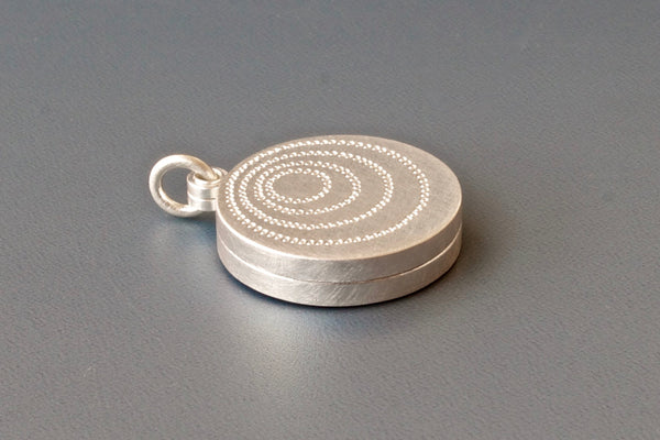 silver double sided photo locket with concentric circles