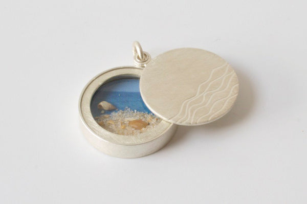 silver floating glass locket filled with seashells with waves design