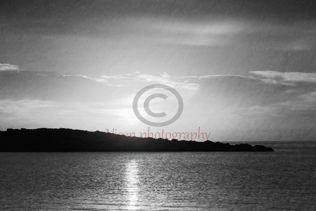 Sunrise behind the island in black and white