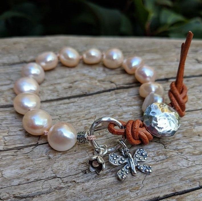 Pink pearl bracelet with butterfly and flower charms and button by Aurora Creative Jewellery
