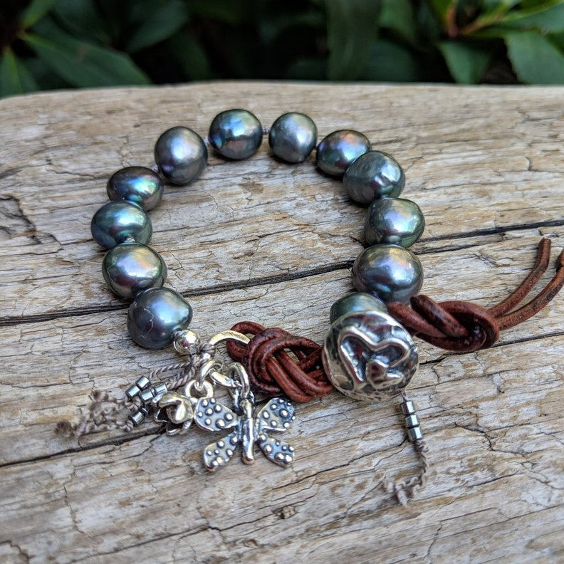 Gray pearl button bracelet with a butterfly and flower charms by Aurora Creative Jewellery