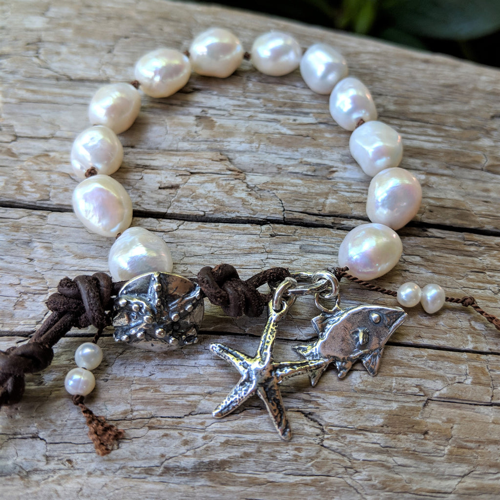 Handmade white baroque pearl bracelet with sterling silver fish and star fish charms and button by Aurora Creative Jewellery