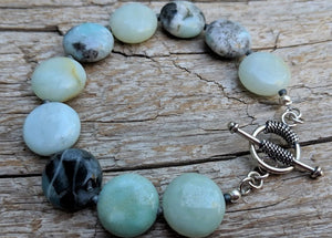 This beautiful handmade artisan toggle bracelet showcases the beauty of natural amazonite gemstone. The calm blues, mints, grays, and natural beiges of amazonite feel refreshing complimented by sterling silver elements. The bracelet was designed with simplicity in mind, to keep the focus on the natural textures of the beautiful stone.