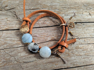 This fun handmade artisan boho leather wrap bracelet showcases the beauty of natural textures. The calm blues, grays, and natural beiges of amazonite gemstone feel refreshing  on the background of natural leather.  The bracelet is finished off with a gold bronze button and leather loop. A heart charm adds another touch of gold and an element of fun. The heart charm can freely move around the bracelet so you can enjoy it from all sides.