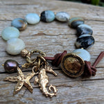 Light blue and gray amazonite stone bracelet with gold bronze seahorse and starfish charms, black pearl, and button, by Aurora Creative Jewellery