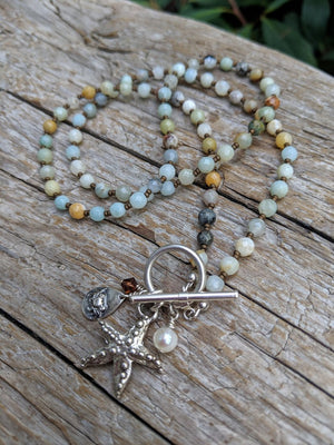 Handmade one-of-a-kind amazonite gemstone ocean necklace with starfish and crab charm pendants.