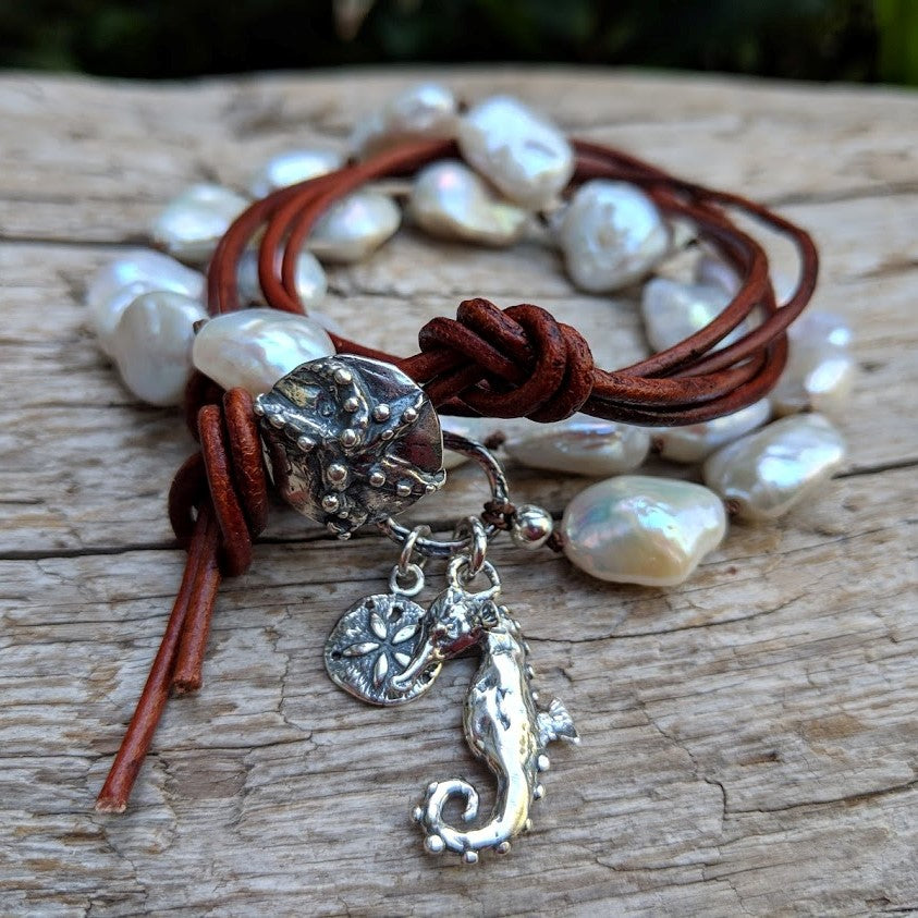 This gorgeous handmade artisan wrap bracelet-necklace combines the beautiful large white baroque pearls with sterling and leather elements. The sterling silver button, seahorse and star charms add a beautiful shine to the combination and create an ocean theme. The bracelet is held together by a silk thread and a brown leather cord. Wearing this bracelet feels like taking a refreshing walk on the beach. By Aurora Creative Jewellery