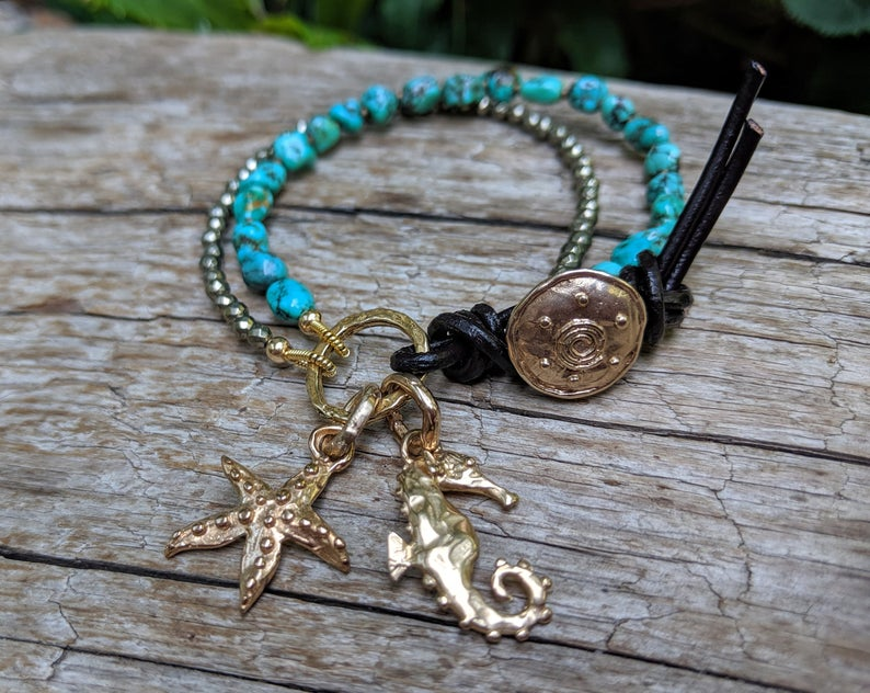 Handmade artisan turquoise gemstone and pyrite button bracelet with gold bronze seahorse and starfish charms by Aurora Creative Jewellery