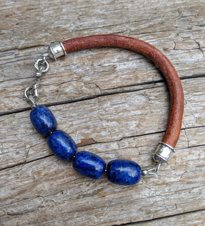 A beautiful handmade artisan bracelet featuring lapis lazuli gemstone combined with thick brown leather and sterling silver elements. The bracelet was designed with simplicity in mind, to keep the focus on the natural textures of the materials.