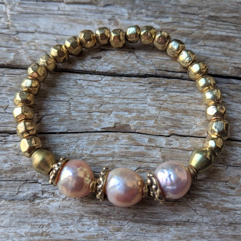 Pink pearl and African brass bracelet with gold bronze. Wear this bracelet alone or in a stack! It is elastic and very easy to put on and take off. By Aurora Creative Jewellery.