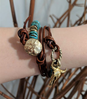 This fun handmade artisan one-of-a-kind wrap bracelet showcases the natural bright Tibetan turquoise, complimented by leather and gold bronze elements. In a modern take on gemstone jewelry we combine charms with leather accents to complement the texture of the stone. The large gold bronze cow skull charm adds a unique touch and creates a western cowgirl theme.