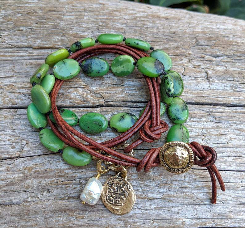 This handmade artisan bracelet combines the gorgeous forest greens of chrysoprase with natural leather, pearl, and gold bronze elements. The brown leather adds a contrasting texture to the combination, while complementing the colors of the stone. The Spanish cross Reale coin charm creates a rustic-medieval theme. A white pearl accent adds a fresh contrast to the combination of natural greens.