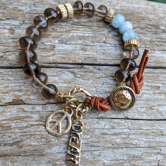 Smoky quartz and aquamarine bracelet with gold bronze peace and dream charms and button, by Aurora Creative Jewellery