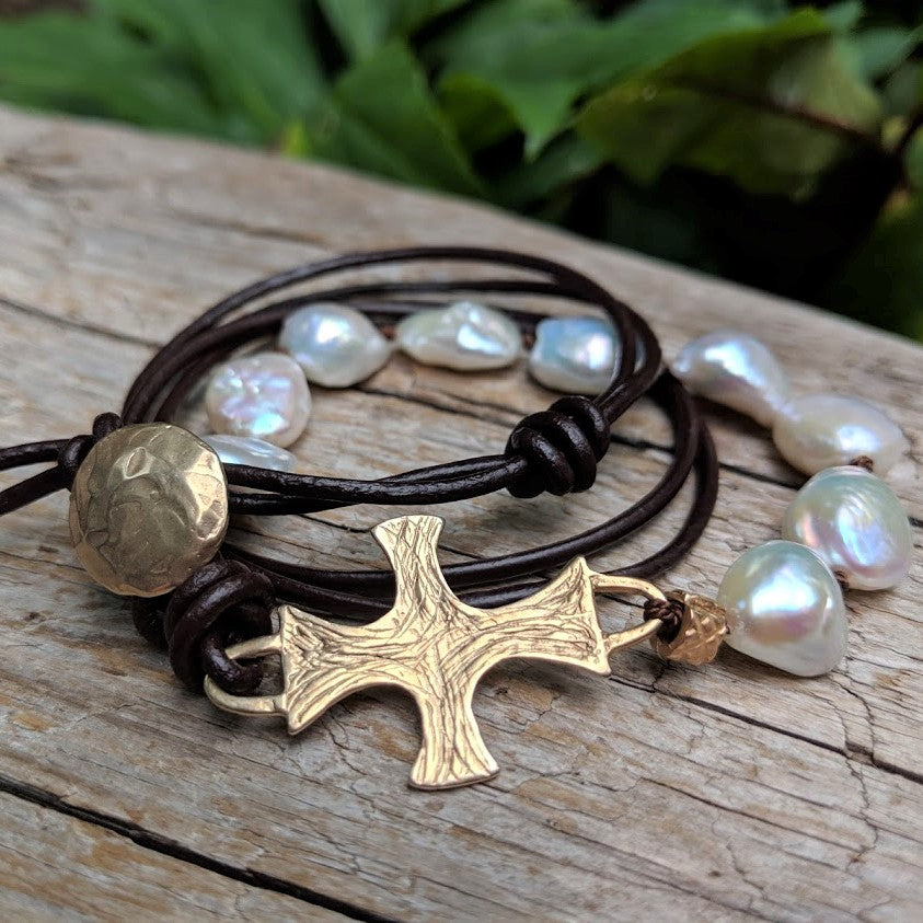 Large white pearl black leather bracelet with gold bronze cross and button, by Aurora Creative Jewellery