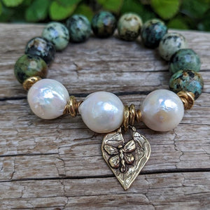 Large white pearl and African turquoise elastic bracelet with heart and butterfly charm by Aurora Creative Jewellery