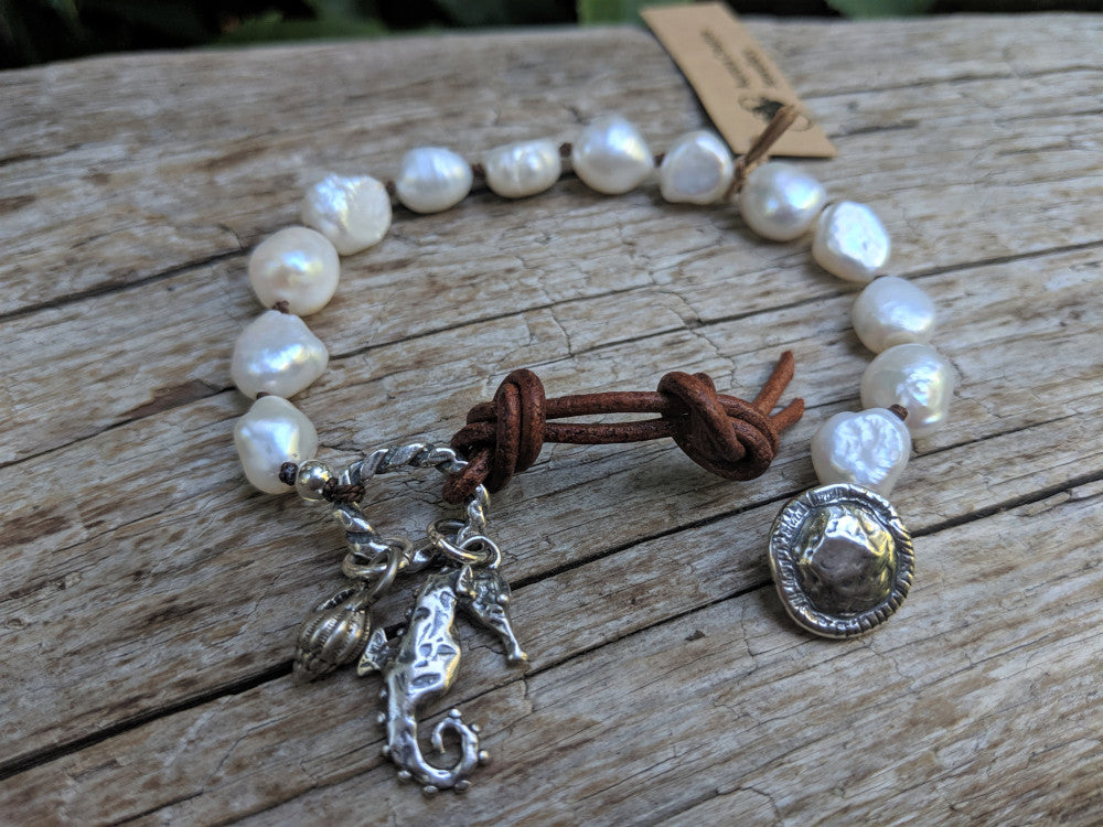 Large white baroque pearl button handmade artisan bracelet with silver seahorse and sea shell charms by Aurora Creative Jewellery
