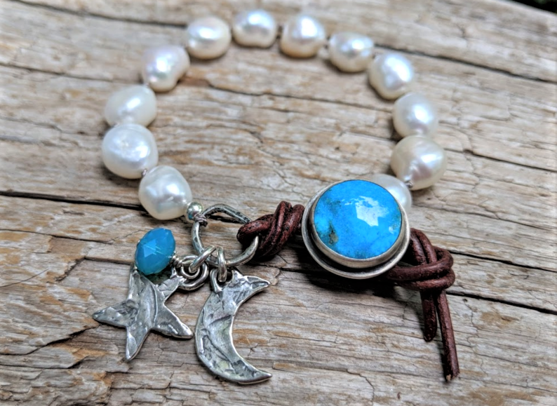 This gorgeous handmade artisan bohemian chic statement bracelet showcases the large white baroque fresh water pearls and contrasting bright turquoise button and artisan sterling silver crescent moon and star charms. The charms create a beautiful night theme and the white pearls resonate with the shine of white moon. A beautiful fresh touch of white pearls on your wrist contrasted by a blue accent is a perfect accessory. The handmade button on this bracelet is unique as it has sterling silver setting.