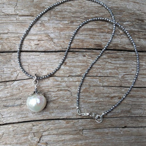 Thin silver hematite gemstone and large white Edison pearl pendant necklace by Aurora Creative Jewellery