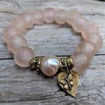 "Pink pearl and sea glass elastic bracelet with gold bronze heart and butterfly with the word ""Inspire"" on the back of the heart. Wear this bracelet alone or in a stack! It is elastic and very easy to put on and take off. By Aurora Creative Jewellery."
