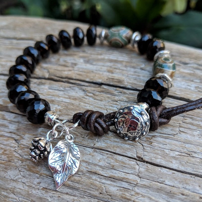 Smoky quartz forest bracelet with silver leaf and pine cone, by Aurora Creative Jewellery