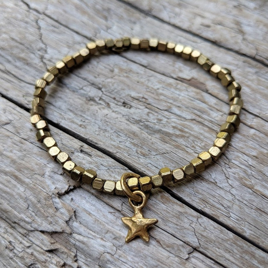 Tiny star delicate African brass bracelet with gold bronze star charm. Wear this bracelet alone or in a stack! It is elastic and very easy to put on and take off. By Aurora Creative Jewellery.