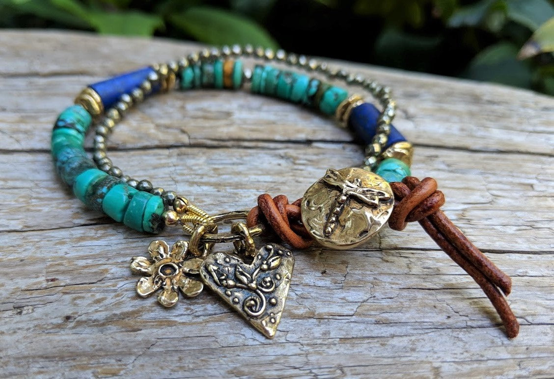 Gorgeous vibrant handmade one-of-a-kind artisan bracelet showcasing the beauty of natural textures. The intoxicating large green Tibetan turquoise beads are complemented beautifully by the deep blue lapiz lazuli, pyrite and brown leather color and texture. Gold bronze elements including the gold bronze flower and floral heart charms and dragonfly button add some shine to the combination.