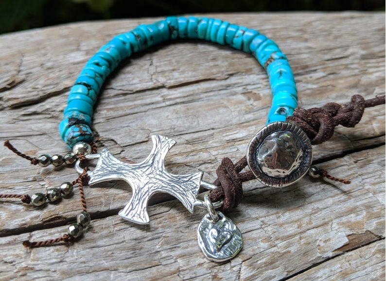 A vibrant modern handmade artisan one-of-a-kind bracelet showcasing the beauty of natural textures. The intoxicating blue turquoise is complemented beautifully by the leather color and texture. Sterling silver cross adds some shine to the combination and creates a religious theme. Tiny pyrite beads add more texture and natural sparkle.