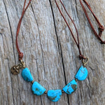 Turquoise leather necklace with gold bronze cross charm, by Aurora Creative Jewellery
