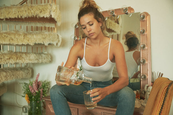 woman pouring Los Sundays tequila