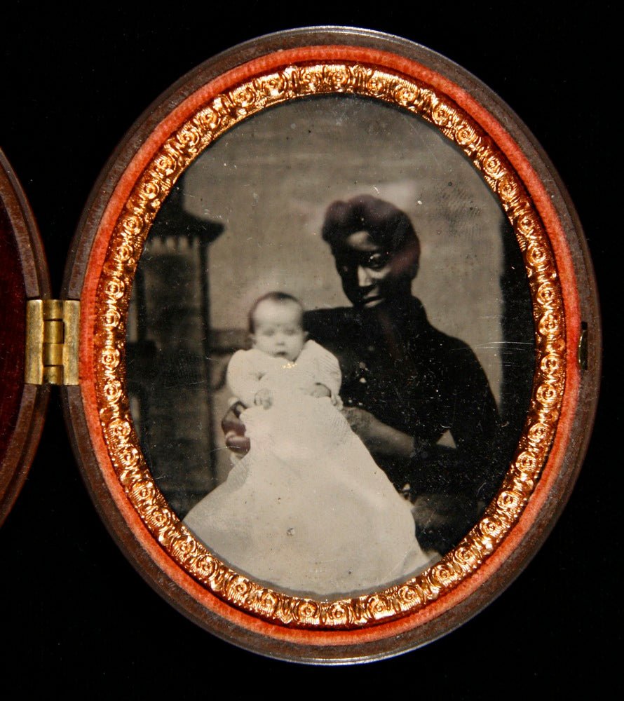 A tintype portrait of a young black woman holding a white child.
