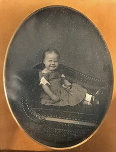 Half plate daguerreotype of a young girl seated on a carved classical sofa.