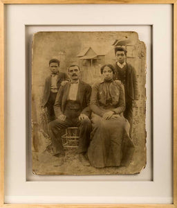A portrait of a black family, grouped together on a late 19th century full glass plate.