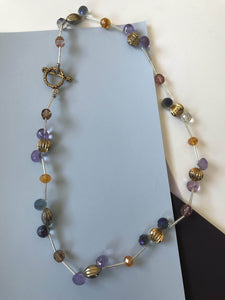 Beaded necklace with amber, quartz, and silver spacer beads.