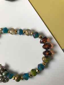 Faceted bracelet with gold spacers and vine decorated bronze clasp.