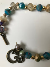 Load image into Gallery viewer, Faceted bracelet with gold spacers and vine decorated bronze clasp.