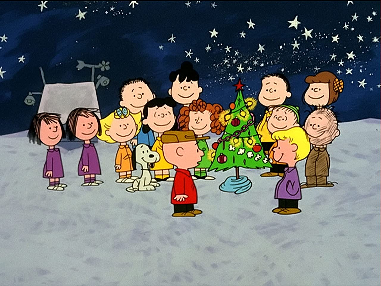 Charlie Brown, Snoopy and friends stand around a Christmas tree in A Charlie Brown movie.
